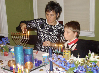 Lighting the menorah with Chris's son Cameron.